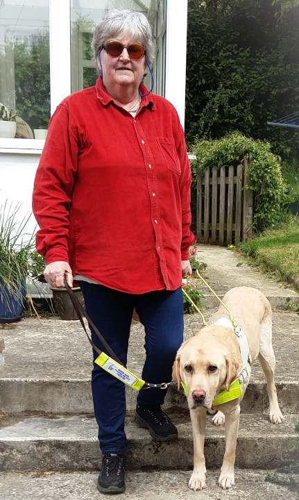 Photo of Sue Allard with her guide dog in the garden